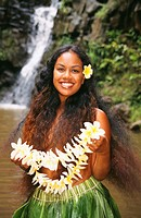 Young Hawaiian woman in ti-leaf skirt stands before a waterfall holding plumeria lei.