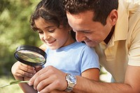 Father and daughter looking at caterpillar through magnifying glass