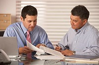 Two businessmen reading papers at desk (thumbnail)