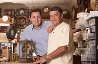 Portrait of father and son fixing clock in repair shop