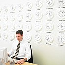 Businessman working with time zone clocks on the wall behind him