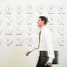 Businessman walking with time zone clocks on the wall behind him
