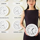 Businesswoman holding clock with time zone clocks on the wall behind him