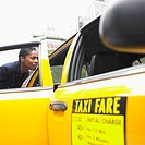 Businesswoman getting into cab