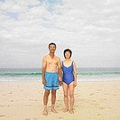 Couple in bathing suits standing at beach