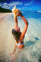 Hawaii, Beautiful young woman pouring water over herself from a conch shell in the shallow water on a tropical beach.