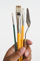 Close up of hands holding paintbrushes and palette knife