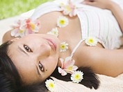 Portrait of woman laying with flowers sprinkled over body