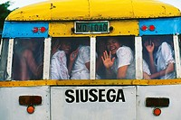 Western Samoa, Apia, Suisega, Samoan children all crowded into the back of bus smiling and waving.