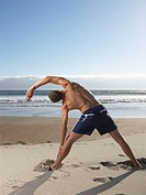 Rear view of man exercising at beach