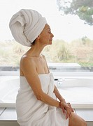 Side view of senior woman wrapped in towel with towel on head