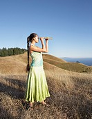 Woman using telescope to view distant hills