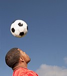 Man bouncing soccer ball off of head