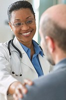 Woman doctor smiling while talking to patient