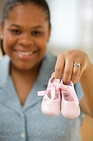 African American woman holding up pink baby shoes