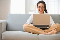 Woman sitting on couch with lap top