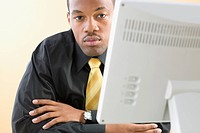 Portrait of businessman sitting at desk in front of computer