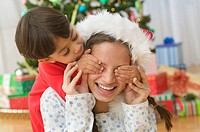 Boy covering older sister´s eyes on Christmas