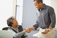 Mature woman sitting at desk shaking man´s hand