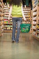 Woman with shopping basket in health food store