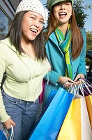 Two women smiling with shopping bags