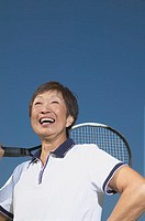 Senior Asian woman smiling with tennis racket