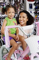 Portrait of mother and young daughter in bike shop