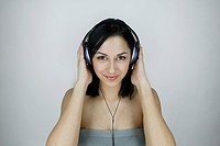 Studio shot of Hispanic woman wearing headphones