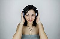 Studio shot of Hispanic woman wearing headphones