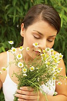 Woman with eyes closed smelling flowers