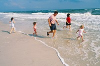 Family running at the surf on a beach in the Gulf Coast of Alabama.