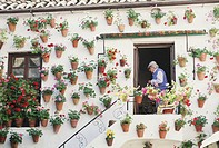 Home with geraniums on exterior, senior man in doorway