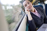 Woman using mobile phone on train, smiling