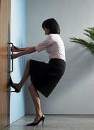 Businesswoman struggling to open door, foot against wall