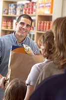 Grocery Store Employee Handing Food to Family
