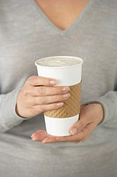 Paper Coffee Cup Held in Woman´s Hands