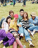 Group of friends on grass, smiling, portrait