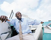 Businessman in convertible with door open, laughing, low angle view