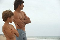 Father and son (8-10) standing on beach, arms folded, profile