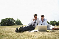 Business couple sitting on grass looking at laptop, smiling