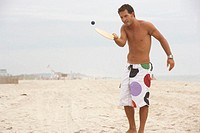 Man playing ping pong on beach, smiling
