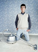 Young man kneeling by vacuum cleaner, portrait