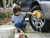 Boy (5-7) washing car wheel with sponge