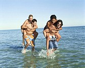 Two men piggybacking women in sea