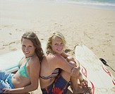 Two young women back to back on beach by surfboards, smiling, portrait