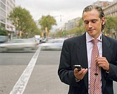 Businessman wearing earphones, holding mobile phone outdoors