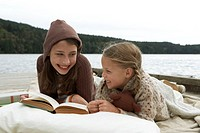 Girls (6-13 years) lying on jetty beside lake, reading book together and smiling