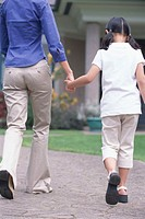 Girl (5-7) walking with mother, holding hands, outdoors, rear view