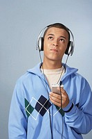 Teenage boy (16-18) listening to personal stereo, looking up