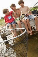 Three boys (5-13) fishing on jetty, arms around each other, laughing
